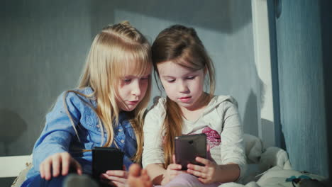 Two-Girls-Play-On-Smartphones-Sit-Side-By-Side-On-The-Bed-In-Your-Bedroom-4K-Video