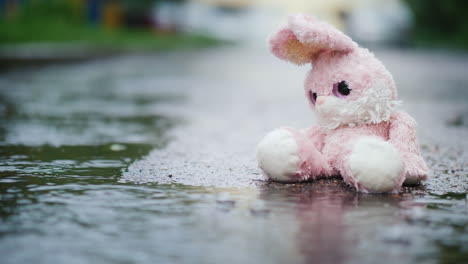 A-Wet-Toy-Hare-Becomes-Wet-Under-The-Rain-Sits-Alone-On-The-Cold-Asphalt-4K-Video