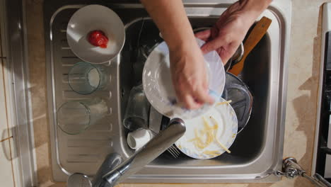 A-Man-Washes-The-Dirty-Dishes-In-His-Kitchen-The-Top-View