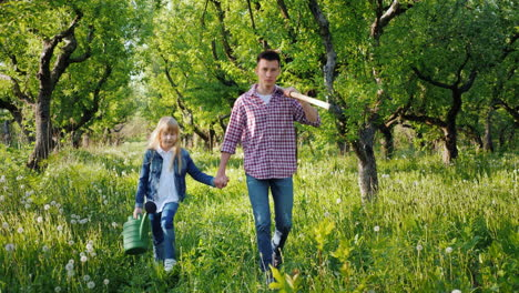 A-Farmer-With-A-Younger-Sister-Walks-Through-The-Apple-Orchard-Carry-A-Scythe-And-Watering-Can