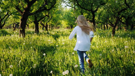 Carefree-Blonde-Girl-Runs-Through-The-Old-Apple-Orchard