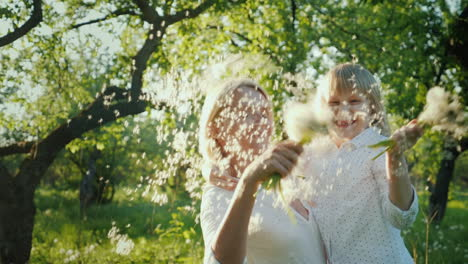 Happy-Together---A-Woman-With-A-Daughter-Playing-With-A-Bunch-Of-Dandelions-Having-Fun