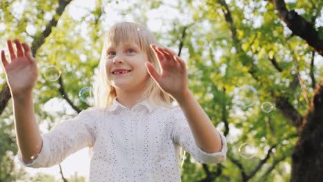 A-Cheerful-Blonde-Girl-Is-Playing-With-Soap-Bubbles-Carefree-Happy-Childhood-Concept-Slow-Motion-Vid