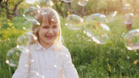 Carefree-Girl-Is-Catching-Soap-Bubbles-Cheerfully-A-Walk-In-The-Spring-Garden-Slow-Motion-Video