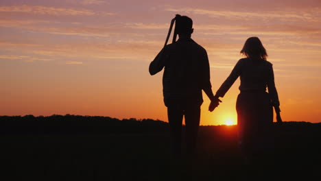 A-Couple-Of-Farmers-Man-And-Woman-Walking-Away-Into-The-Field-At-Sunset-A-Man-Carries-A-Braid-On-His