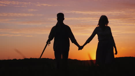 A-Young-Couple-Of-Farmers-Walking-Across-The-Field-To-Meet-The-Camera-Silhouettes-At-Sunset-4K-Video