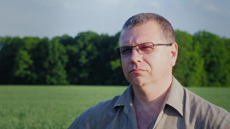 Portrait-Of-A-Farmer-In-Glasses-On-The-Background-Of-A-Green-Field-4K-Video