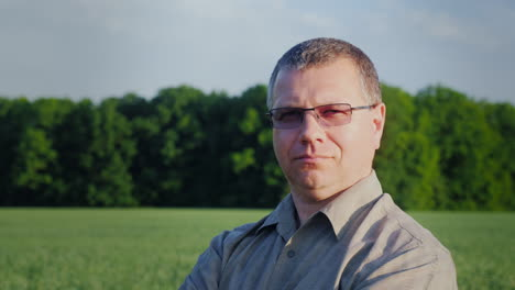 Portrait-Of-A-Successful-Farmer-Looking-At-The-Camera-Against-The-Background-Of-A-Green-Wheat-Field-