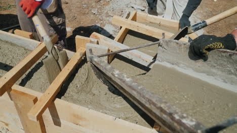 Work-With-Concrete-At-The-Construction-Site-Workers-Take-Concrete-Into-A-Wooden-Mold-Heavy-Manual-La