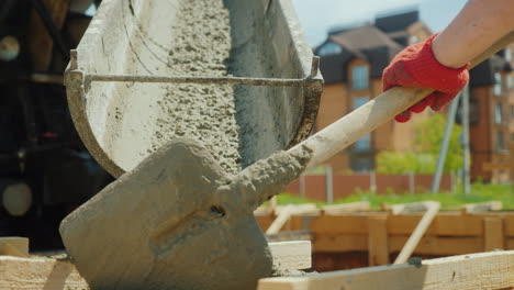 Pour-Concrete-From-The-Mixer-Into-The-Formwork-In-The-Background-Blurred-New-Buildings-Construction-
