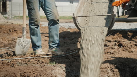 Pouring-Concrete-Into-The-Foundation-From-The-Gutter-Concrete-Flows-Next-To-The-Worker-With-A-Shovel