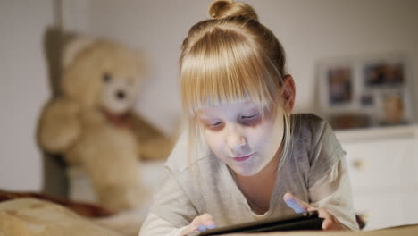 Portrait-Of-A-Child-Enjoying-A-Tablet-With-A-Bedroom-Lies-On-His-Bed-In-The-Evening