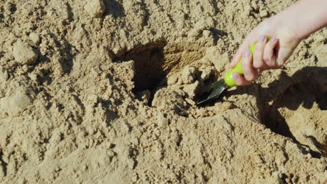 A-Hand-With-A-Small-Garden-Shovel-Gathers-Sand-From-A-Large-Pile