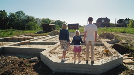 The-Family-Is-On-The-Foundation-Of-Their-Future-Home-New-Beginnings-Concept