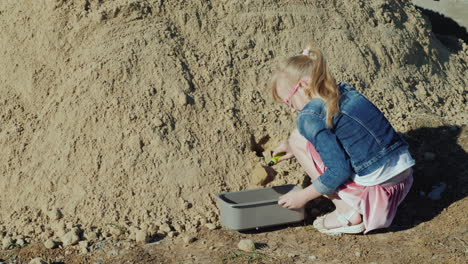 The-Girl-Pours-Sand-Into-The-Flower-Pot-Amateur-Gardening