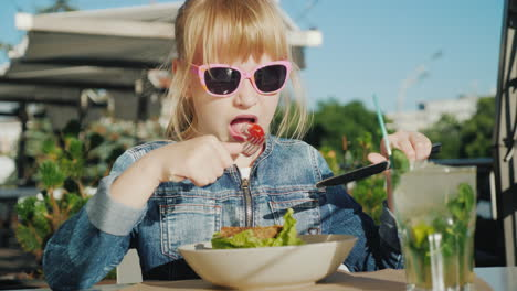A-Girl-In-Pink-Glasses-Is-Eating-A-Salad-On-The-Summer-Playground-Of-A-Cafe-Summer-Holiday-With-Kids