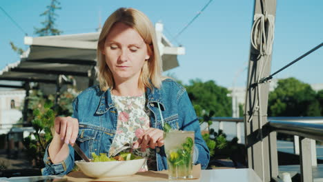A-Young-Woman-Is-Eating-A-Salad-On-The-Summer-Terrace-In-A-Restaurant-Eat-Outdoors-4K-Video