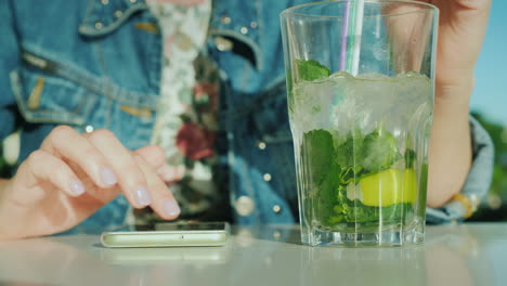 A-Woman-Uses-A-Smartphone-Next-Is-A-Glass-With-A-Cool-Cocktail-In-The-Frame-Are-Visible-Only-Hands