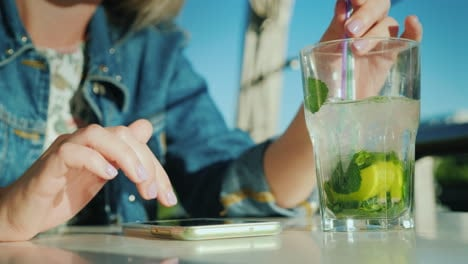 A-Woman-Is-Using-A-Smartphone-In-A-Cafe-There-Is-A-Glass-With-A-Cocktail-Beside-Her-To-Rest-And-Busi