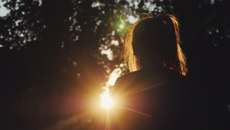 Silhouette-Of-A-Girl-Looking-At-The-Sunset-In-The-Park-The-Sun-Beautifully-Illuminates-Her-Blond-Hai