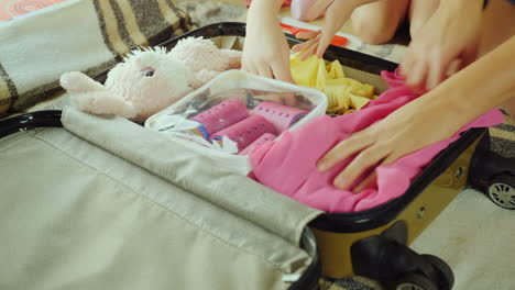 Mom-And-Daughter-Are-Going-On-Vacation-Two-Pairs-Of-Hands-Put-Things-And-Toys-In-A-Travel-Bag-4K-Vid