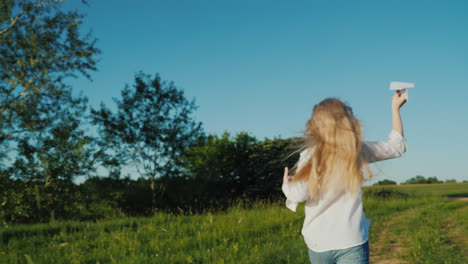 A-Girl-With-Long-Hair-Runs-With-A-Paper-Airplane-In-Her-Hand-Baby-Dreams-Concept-Steadicam-Shot