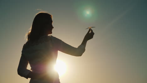 A-Woman-Is-Playing-With-A-Paper-Airplane-It-Stands-In-The-Rays-Of-The-Setting-Sun-Dreams-About-Vacat