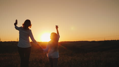 Mom-And-Daughter-Are-Playing-Paper-Airplanes-At-Sunset-In-A-Picturesque-Place-Happy-Time-With-The-Ba