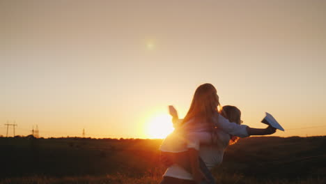 The-Girl-Is-Sitting-On-Her-Mother-s-Shoulders-Playing-With-Paper-Airplanes-A-Happy-Family-4K-Video