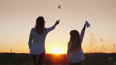 Mom-And-Daughter-Launch-Paper-Airplanes-Into-The-Air