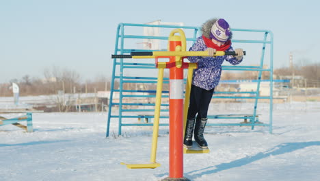 A-Girl-In-Warm-Clothes-Is-Playing-In-The-Schoolyard-Riding-A-Fitness-Trainer