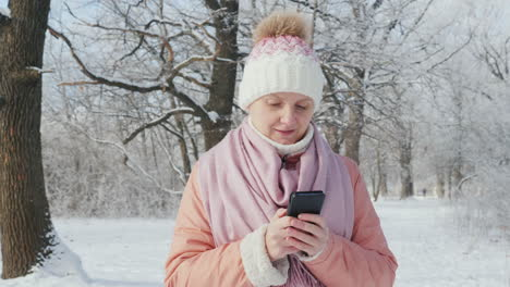 A-Woman-In-A-Pink-Jacket-Enjoys-A-Walk-In-A-Winter-Park-Uses-A-Mobile-Phone-4K-Slowm-Motion-Video