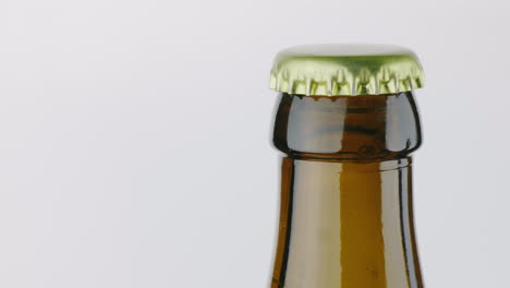 The-Neck-Of-A-Bottle-Of-Beer-Is-Covered-With-A-Metal-Lid-On-A-White-Background-4K-Video