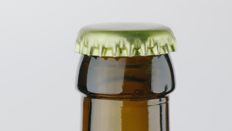 The-Neck-Of-A-Bottle-Of-Beer-Is-Covered-With-A-Metal-Lid-On-A-White-Background
