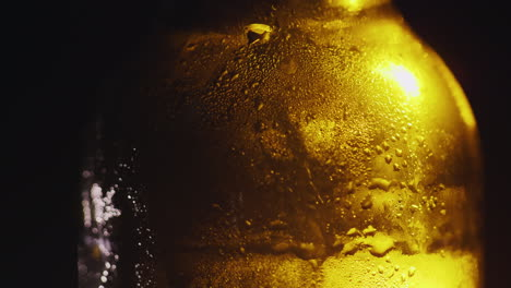Close-Up-Of-A-Glass-Bottle-With-Drops-Of-Condensed-Water-Cold-Drink-Concept-On-A-Black-Background-4K