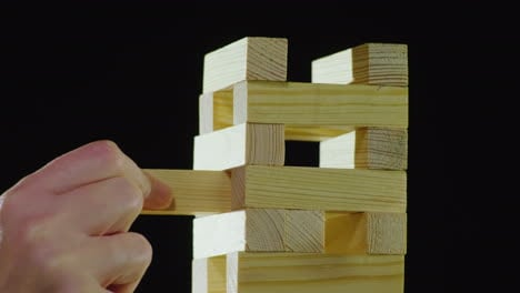 The-Hand-Pulls-A-Wooden-Block-From-The-Tower-Playing-In-Djanga-Board-Games-Concept