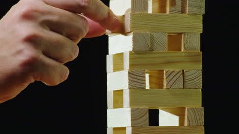 Two-People-Take-Turns-Pulling-Out-Wooden-Bars-From-The-Tower-Playing-In-Jenga