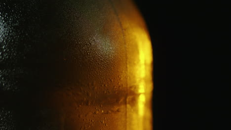 A-Bottle-Of-Cold-Beer-With-Droplets-Of-Water-Slowly-Rotates-Is-Illuminated-By-A-Ray-Of-Light-On-A-Bl