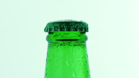The-Neck-Of-A-Green-Bottle-With-A-Cold-Drink-Covered-With-Droplets-Of-Water-Slowly-Rotating-On-A-Whi