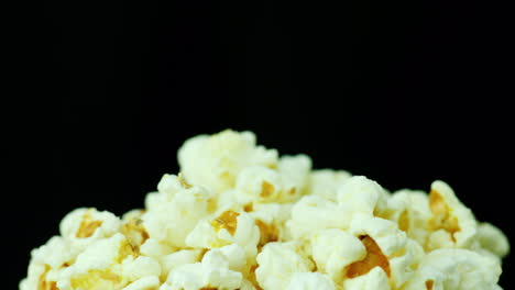 A-Bunch-Of-Popcorn-On-A-Black-Background-Slowly-Rotates-4K-Video