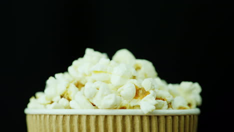 A-Paper-Glass-Of-Popcorn-Slowly-And-Smoothly-Rotates-On-A-Black-Background-4K-Video