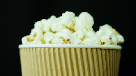 A-Glass-Of-Mouth-Watering-Popcorn-Smoothly-Rotates-Against-A-Black-Background-Food-For-Watching-Movi