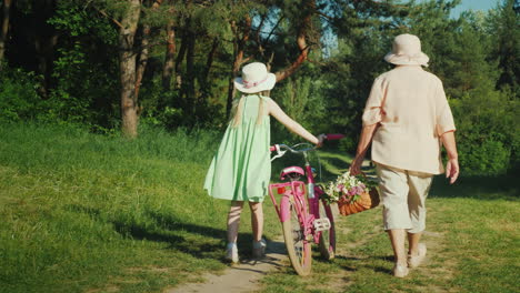 Grandma-Is-Walking-With-Her-Granddaughter-The-Girl-Drives-A-Bicycle-The-Grandmother-Carries-A-Basket