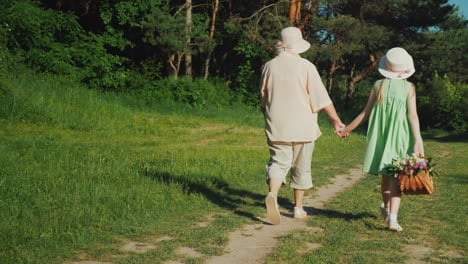 Grandmother-Is-Walking-With-Her-Granddaughter-In-The-Forest-Holding-Hands-The-Girl-Carries-A-Basket-