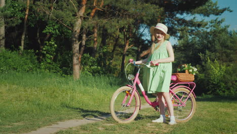 A-Girl-In-A-Summer-Dress-Is-Standing-Near-A-Bicycle-Looking-At-The-Camera-With-Her-Basket-Of-Wildflo