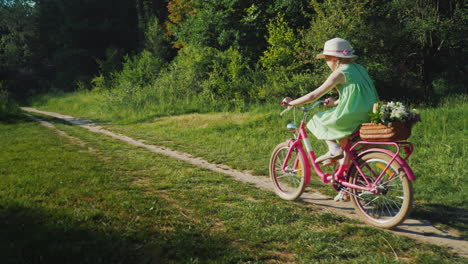 A-Girl-In-A-Green-Summer-Dress-Is-Riding-Along-A-Path-In-The-Forest-Carries-A-Basket-Of-Flowers-Acti