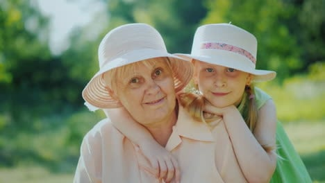 Portrait-Of-A-Happy-Elderly-Woman-With-Her-Granddaughter-Smiling-Looking-At-The-Camera-4K-Video