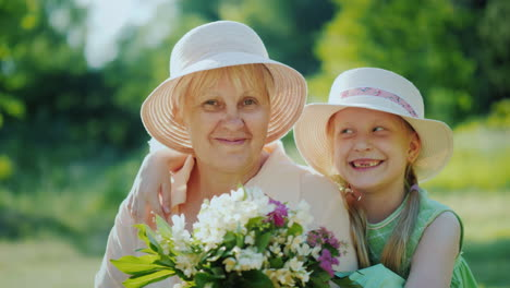 Portrait-Of-A-Happy-Elderly-Woman-With-Her-Granddaughter-Hold-A-Basket-With-Wild-Flowers-Look-At-The