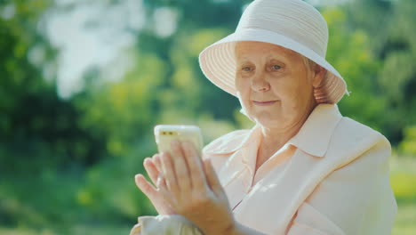 An-Elderly-Woman-In-Summer-Clothes-And-A-Hat-Uses-A-Smartphone-Relax-In-The-Summer-Park-4K-Video