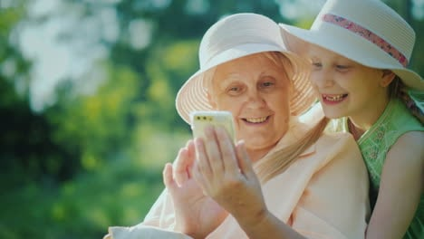 Happy-Girl-With-Grandmother-Looking-At-The-Smartphone-Screen-Together-Have-A-Rest-Together-In-A-Summ